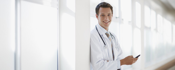 Doctor with cell phone in hospital corridor