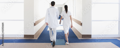 Doctor and nurse walking in hospital corridor
