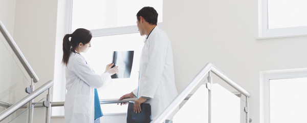 Doctors reviewing x-ray on stairs
