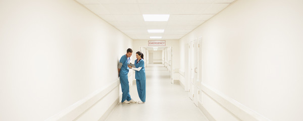 Nurses looking at medical chart in hospital corridor