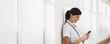 Nurse with text phone in hospital corridor