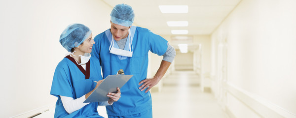 Surgeons with clipboard in hospital corridor