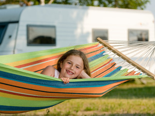 Summer camping - cute girl in colorful hammock