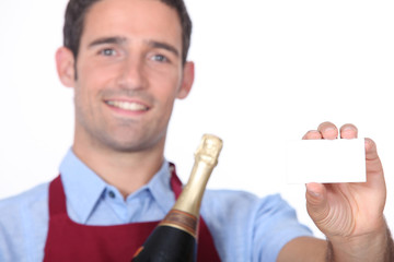 A sommelier holding up a blank business card