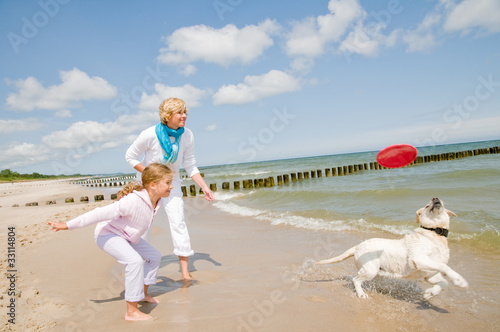 Family playing with dog at the beach