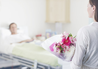 Woman bringing flowers to man in hospital