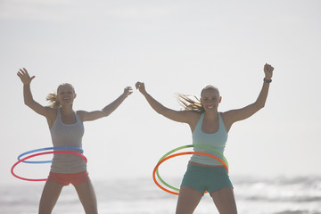 Women playing with plastic hoops on beach