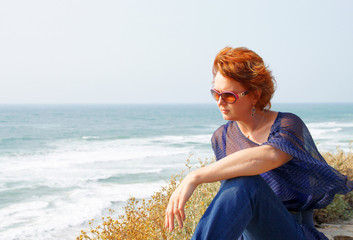 Beautiful middle-aged woman sits by the sea