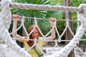 aadventure woman on jungle rope bridge