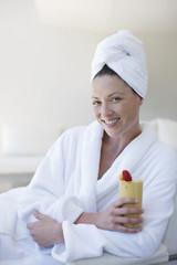 Woman in bathrobe drinking smoothie