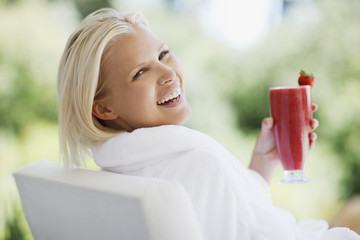 Woman in bathrobe drinking smoothie