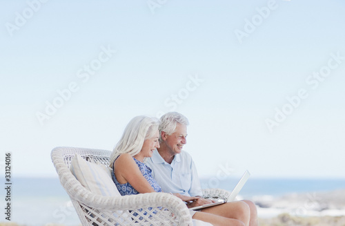 Couple using laptop on beach patio