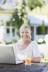 Woman using laptop at patio table