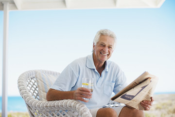 Senior man reading newspaper on beach patio
