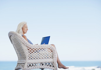 Senior woman using laptop on beach patio