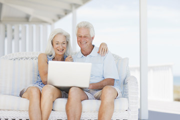Senior couple using laptop on patio