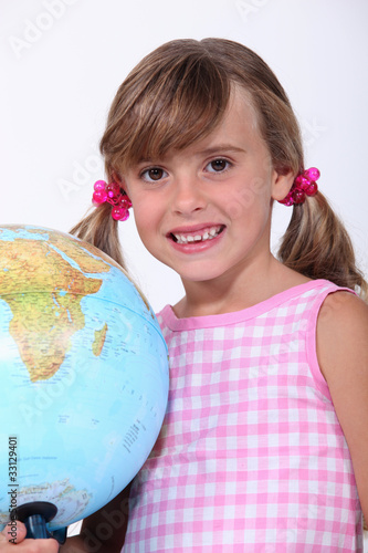 Young schoolgirl with a large globe