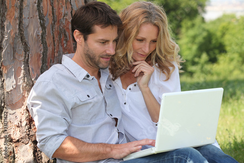 Couple in park on laptop computer