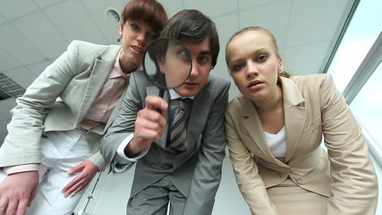 Three managers inspecting something and pointing at it in office