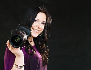 photographer woman holding camera over dark background