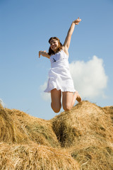 Jumping   girl over hay