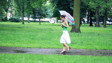 Woman walking with colorful umbrella, slow motion