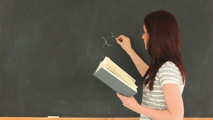 Charming woman writing a mathematical formula on a blackboard