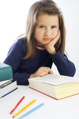 sechsjähriges Mädchen sitzt lustlos vor einem Buch (mr)