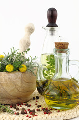Mortar and pestle with herbs and bottles of olive oil