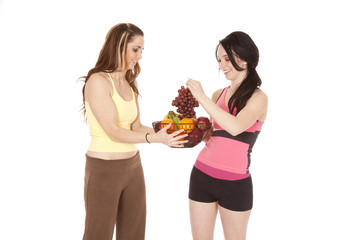two women one holding grapes