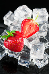 Fresh ripe strawberries with ice cubes on black surface