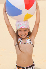 Little at the beach holding inflatable ball above head