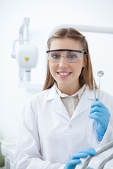 Smiling dentist with safety goggles holding dental tools