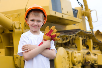 Boy is against the background of excavator.