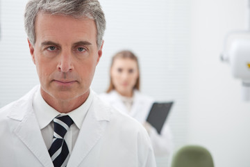 Serious man in lab coat with woman in background