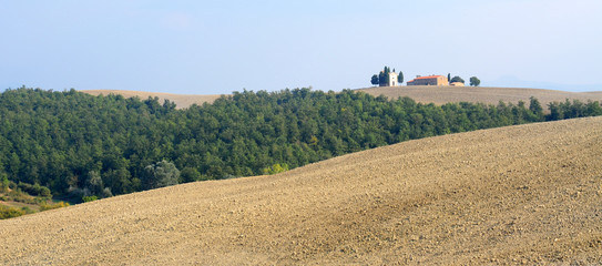 Tuscan landscape with fields, trees and farmhouse