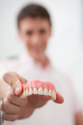 Man in dentist's office holding false teeth