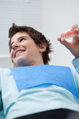 Boy in dentist's chair holding false teeth