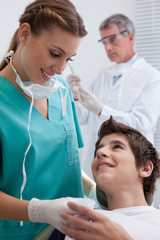 Dentist's assistant giving boy in chair beaker