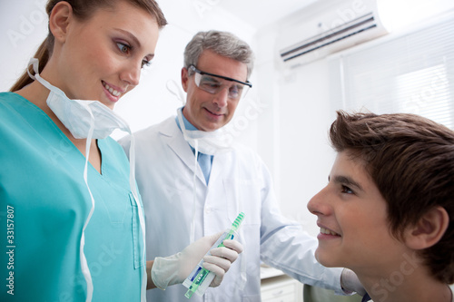 Dentist's assistant holding toothbrush and toothpaste talking to boy
