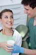Dentist giving beaker to woman in chair
