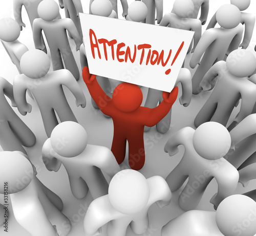 Person Holding Attention Sign in Crowd to be Recognized