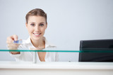 Smiling receptionist holding health insurance card