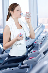 Young woman at the gym exercising. Drink