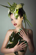 Beauty Frau mit grünem Kopfschmuck blickt sexy