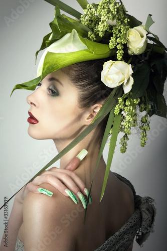 Beauty Frau mit grünem Kopfschmuck blickt in die Ferne