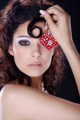 Hübsche Frau mit Studio Make Up und rotem Schmuck Herz auf Auge