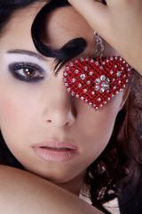 Hübsche Frau mit rotem Schmuck Herz auf Auge close up