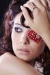 Hübsche Frau mit Make Up und rotem Schmuck Herz fern blickend