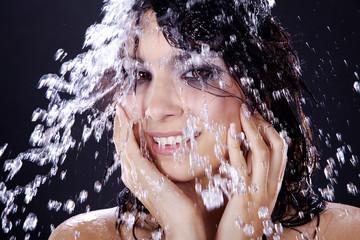 Hübsche Frau duscht unter einem Wasserfall